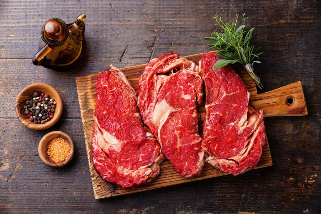 Raw fresh meat Ribeye steak entrecote and seasoning on dark wooden background